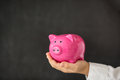 Piggy bank in hand against blackboard blank Royalty Free Stock Photography