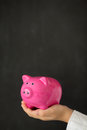 Piggy bank in hand against blackboard blank Royalty Free Stock Photos
