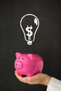 Piggy bank in hand against blackboard with drawing bulb lamp idea concept Stock Images