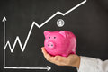 Piggy bank in hand against blackboard with growing chart Stock Photo