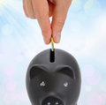 Piggy bank and hand with coin saving putting a into Stock Photo