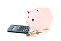 Piggy bank with house keys and calculator isolated on white Stock Photography