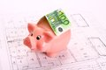 Piggy bank with hundred euro bill as roof on house drawing top view Royalty Free Stock Photography