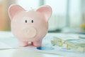 Piggy bank image of pink and dollar bills near by Stock Image