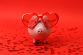 Piggy bank in love with red heart sunglasses standing on red background with shining red heart glitters horizontal Stock Image