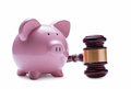 Piggy bank next to a wooden judge gavel porcelain pink concept of savings economic litigations and auctions close up with shadow Royalty Free Stock Image