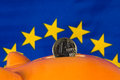 Piggy bank with one euro coin, EU flag in background Royalty Free Stock Photo