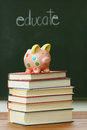 Piggy bank on a pile of books in front blackboard Royalty Free Stock Photo