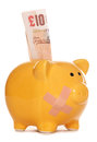 Piggy bank with plaster and ten pound note Royalty Free Stock Photo
