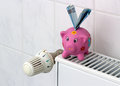 Piggy bank with radiator thermostat saving heating costs save energy euro banknotes next to a on the Stock Image