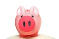 Piggy bank on sand Royalty Free Stock Photo