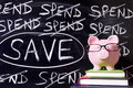Piggy bank with savings message pink glasses standing on books next to a blackboard untidy spending and saving Stock Image