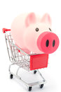 Piggy bank in shopping cart on white background Royalty Free Stock Photos