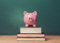 Piggy bank on top of books with chalkboard creating a cost of education theme Royalty Free Stock Photo