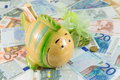 Piggy bank on top euro bills toy fish of Stock Photo