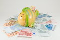 Piggy bank on top euro bills toy fish of Royalty Free Stock Photos