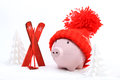 Piggy box with red hat with pompom standing next to red ski and ski sticks on snow and around are snowbound trees Royalty Free Stock Photo