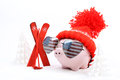 Piggy box with red hat with pompom and sunglasses shape heart with usa flag standing next to red ski and ski sticks on snow and ar Stock Photography