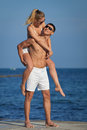 Piggyback attractive couple in sunglasses on background of sky Royalty Free Stock Photography