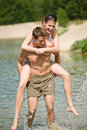 Piggyback - happy couple enjoy sun at lake Royalty Free Stock Image
