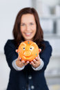 Piggybank conceptual portrait of smiling businesswoman shows the Stock Photos