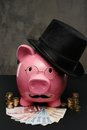 Piggybank in glasses and hat with pile of coins and banknotes Royalty Free Stock Photography