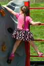 Pigtail Girl Climbing a Rock Wall Royalty Free Stock Photo