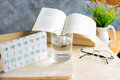 a piils of drug for weekly with water and book with glasses on t Royalty Free Stock Photo