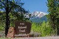 Pike national forest sign a colorado with the snow caped rocky mountains and Royalty Free Stock Photo