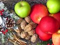 A pile of autumn fruit top view on brass table background. Green red apples, walnuts and a bunch of cinnamon . Rustic style photo. Royalty Free Stock Photo