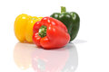 Pile of bell peppers green yellow and red on white background with reflection Royalty Free Stock Photos