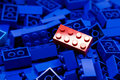 Pile of blue color building blocks with selective focus and highlight on one particular red block using available light Royalty Free Stock Photo