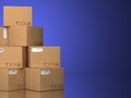 Pile of cardboard boxes on a blue background. Royalty Free Stock Photo