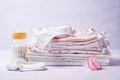 Pile of childrens clothing with a bottle of milk and pacifier Royalty Free Stock Photo