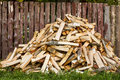 Pile of chopped firewood lies near the fence at the house Royalty Free Stock Photography