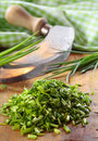 Pile of chopped fresh chives lying on a wooden kitchen table with a curved chopping knife and checked green and white cloth Stock Photos