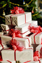 Pile of christmas presents present with ribbons and bows tree in background Royalty Free Stock Images