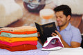 A pile of clothes next to the iron with gorgeous man smiling behind while he is reading a book Royalty Free Stock Photo