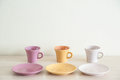 Pile of colorful modern cups of coffee on wooden table Royalty Free Stock Photo