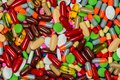 Pile of colorful tablets and capsule pills. Full frame of medicine, vitamins and supplements. Top view many of pills background.