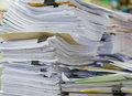 Pile of documents on desk stack up high waiting to be managed Royalty Free Stock Photo