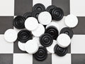 Pile of draughts on checkerboard black and white Royalty Free Stock Image