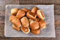 Pile fresh baked dinner rolls of on a sheet of parchment paper top view in horizontal format Stock Image