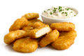 Pile of golden deep fried battered chicken nuggets with bowl of tartar sauce isolated on white Royalty Free Stock Images