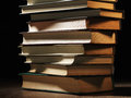 Pile of hardcover books in a shadowy room stacked on top one another on wooden desk with copyspace the foreground Royalty Free Stock Photos
