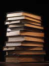 Pile of hardcover books in a shadowy room stacked on top one another on wooden desk with copyspace the foreground Stock Photos
