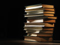 Pile of hardcover books in a shadowy room stacked on top one another on wooden desk with copyspace the foreground Royalty Free Stock Image
