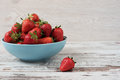 Pile of juicy ripe organic fresh strawberries in a large blue bowl. Light rustic wooden background. Royalty Free Stock Photo