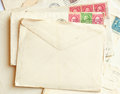 Pile of letters, post stamps and blank envelope
