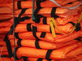 Pile of life jackets ready for shipping close up view packed orange string with hook holding jacket safety control on board ship Royalty Free Stock Photos